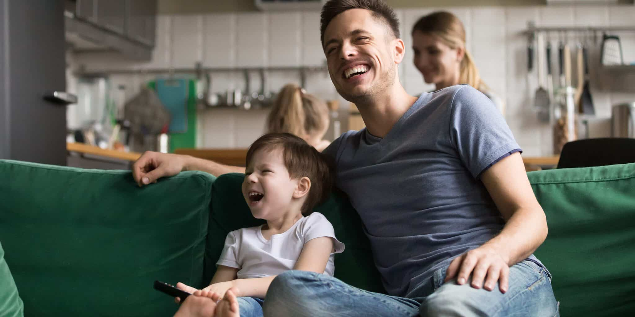Happy dad and kid son laughing watching tv together